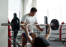 Muscular coach insures athlete exercising with barbell